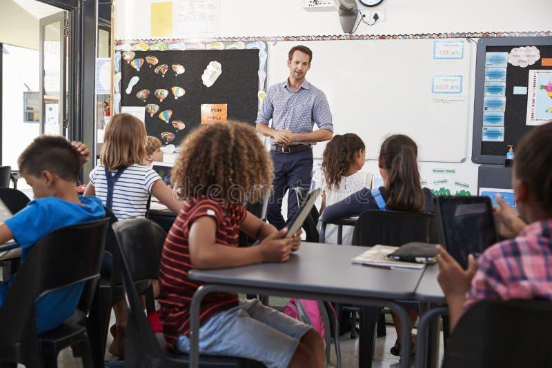 Lehrer, der vor grundlegender Schulklasse steht stockfotos