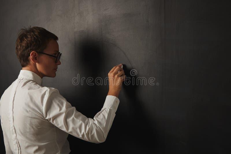 Lehrer in der weißen Bluse an der Tafel stockbild