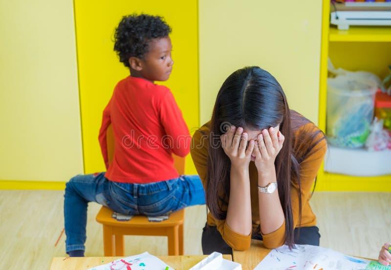 Lehrer erhalten Kopfschmerzen mit zwei frechen Kindern im Klassenzimmer an der Kindergartenschule stockfotografie