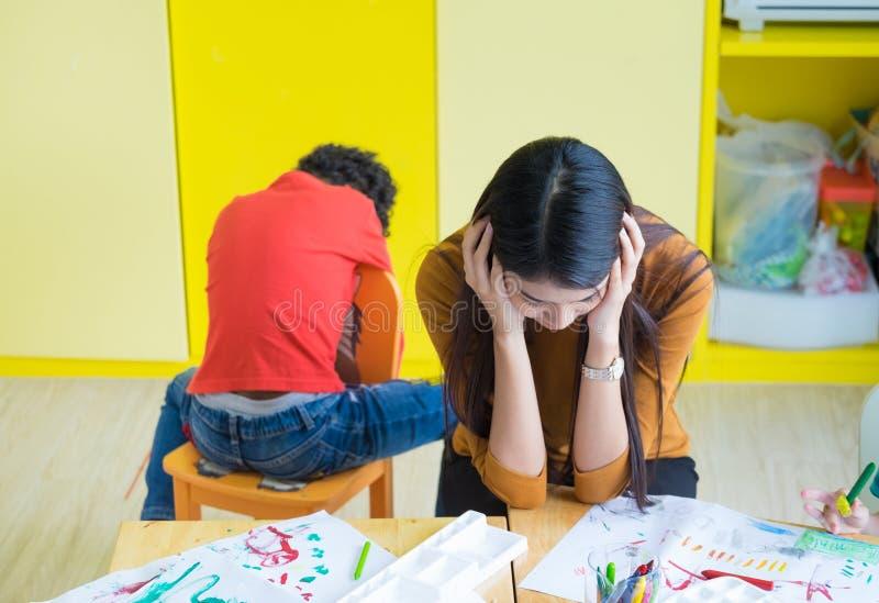 Lehrer erhalten Kopfschmerzen mit zwei frechen Kindern im Klassenzimmer an der Kindergartenschule stockfoto