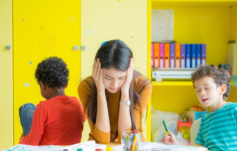 Lehrer erhalten Kopfschmerzen mit zwei frechen Kindern im Klassenzimmer am kinde lizenzfreie stockbilder
