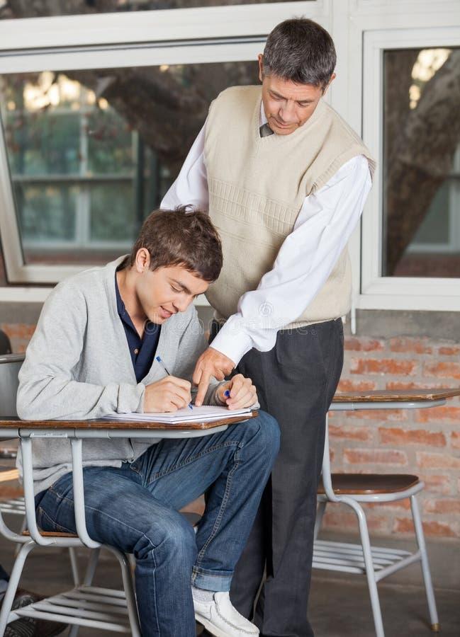 Lehrer-Explaining Test To-Student In Classroom lizenzfreies stockbild