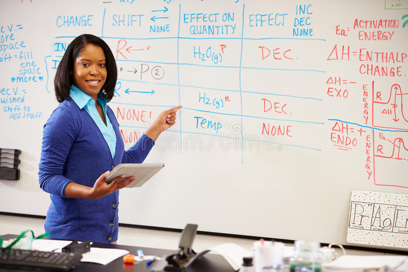 Lehrer für Wissenschaft Standing At Whiteboard mit Digital-Tablet stockbilder