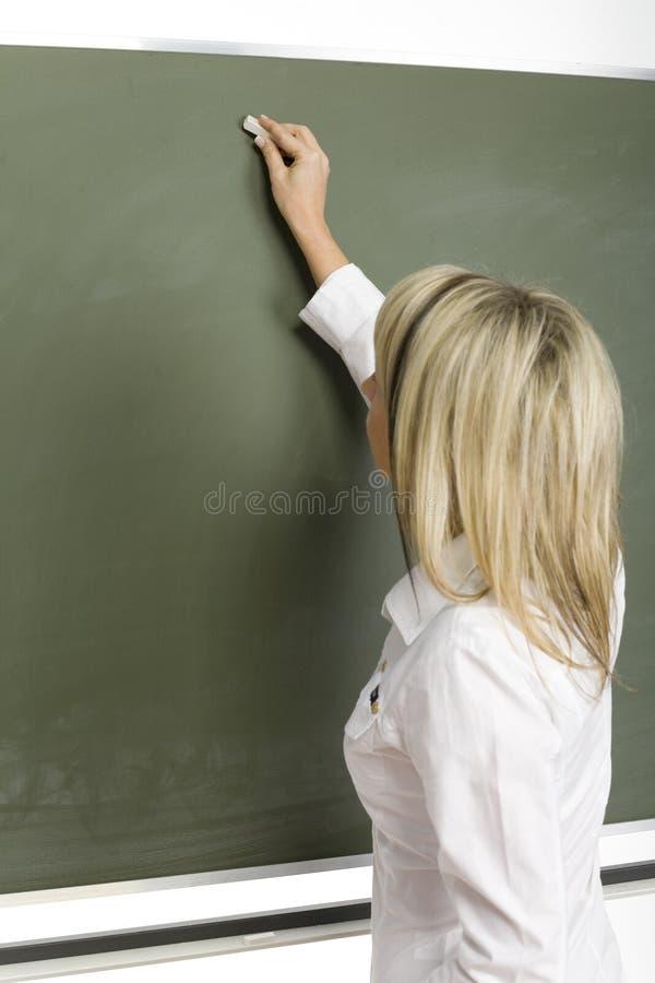 Lehrer am greenboard stockbilder