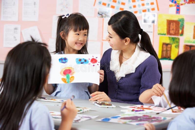 Lehrer-helfende Kursteilnehmer in der chinesischen Schule stockfotografie