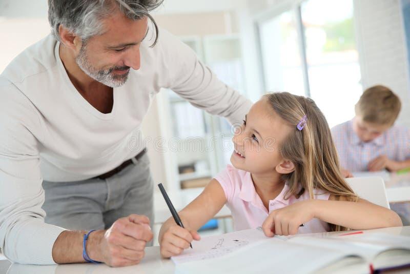Lehrer-Helping Pupils In-Klasse stockbild