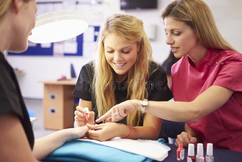 Lehrer Helping Students Training, zum Kosmetiker zu werden lizenzfreie stockfotos