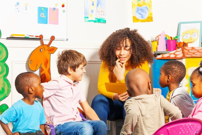 Lehrer im Kindergarten ein Buch zu den Kindern lesend lizenzfreie stockfotos