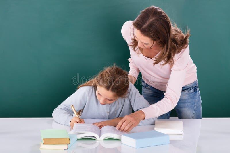 Lehrer Looking At Student, das Klassen-Arbeit erledigt lizenzfreies stockbild