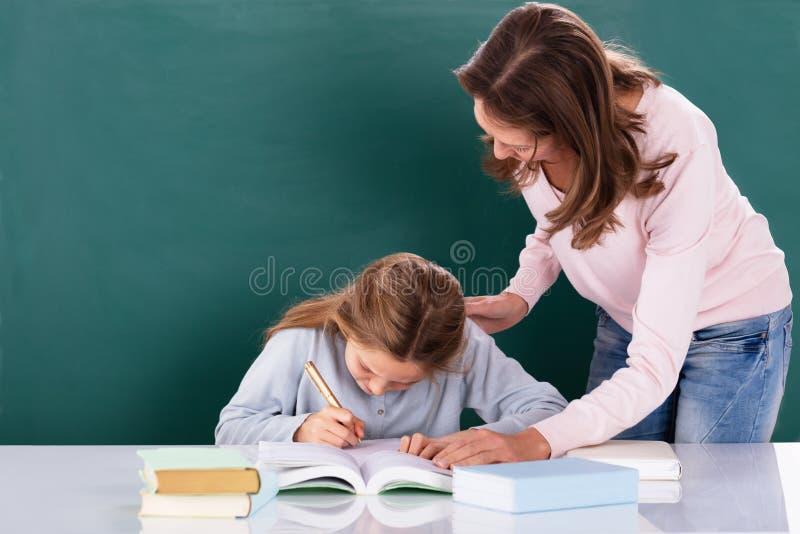 Lehrer Looking At Student, das Klassen-Arbeit erledigt lizenzfreie stockfotografie