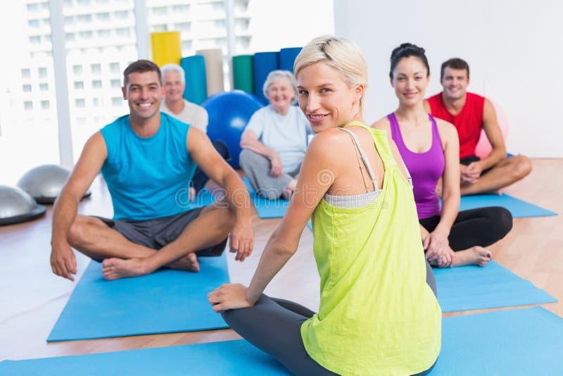 Lehrer mit übendem Yoga der Klasse im Eignungsstudio lizenzfreies stockfoto