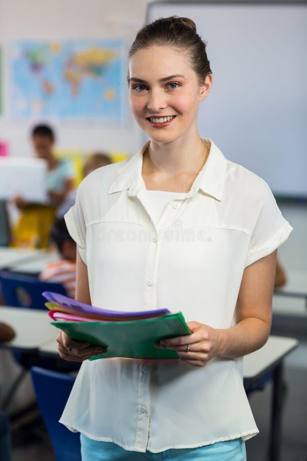 Lehrer mit den Dateien, die im Klassenzimmer stehen lizenzfreie stockfotos