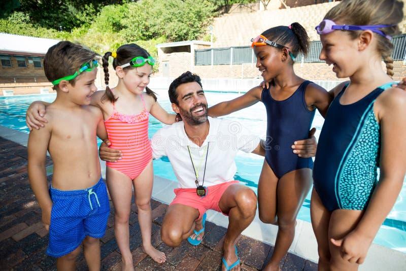 Lehrer mit den kleinen Schwimmern, die am Poolside stehen lizenzfreies stockfoto
