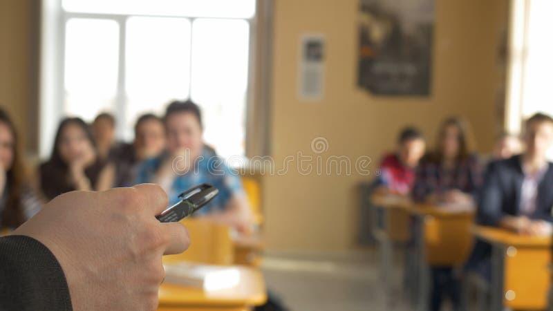 Lehrer mit einer Gruppe hohen Schülern im Klassenzimmer Ansicht von den Händen des Lehrers, der den Vortrag erklärt lizenzfreie stockfotografie