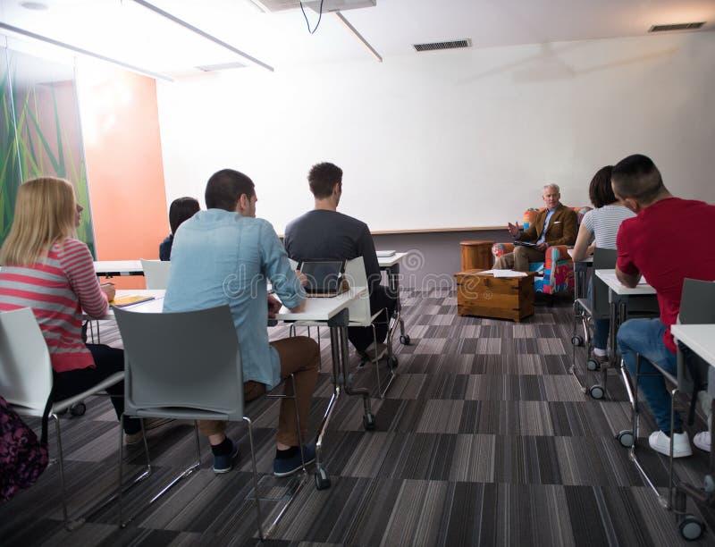 Lehrer mit einer Gruppe Studenten im Klassenzimmer lizenzfreies stockbild