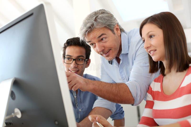 Lehrer mit Paaren von Studenten vor Computer stockbilder