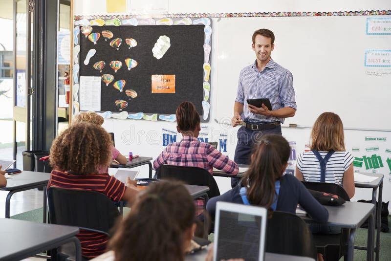 Lehrer mit Tablette vor grundlegender Schulklasse stockfotografie