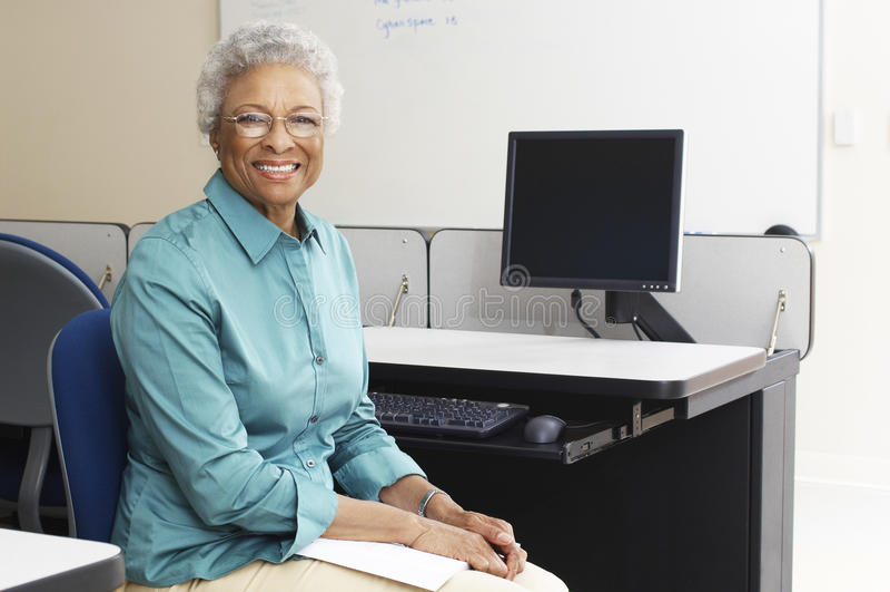 Lehrer Sitting In Classroom lizenzfreie stockfotografie