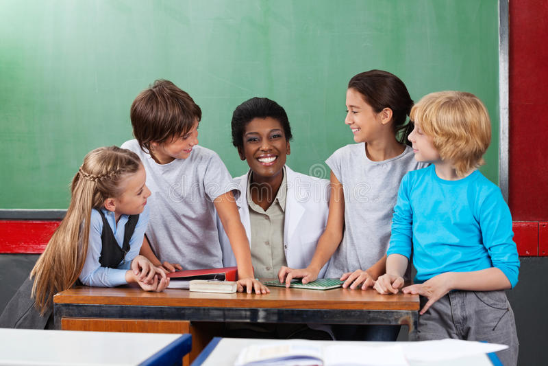 Lehrer Sitting At Desk mit Studenten am Schreibtisch lizenzfreie stockfotos