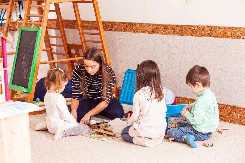 Lehrer spielt mit Kindern lizenzfreie stockfotos
