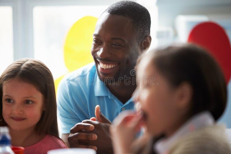 Lehrer-Supervising Children Eating-Schulmahlzeit stockbilder