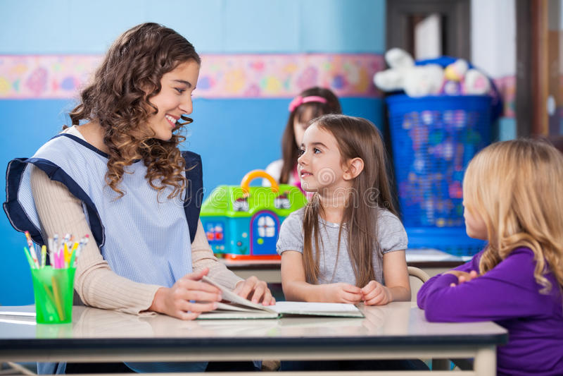 Lehrer Teaching Little Girls im Klassenzimmer lizenzfreie stockfotos