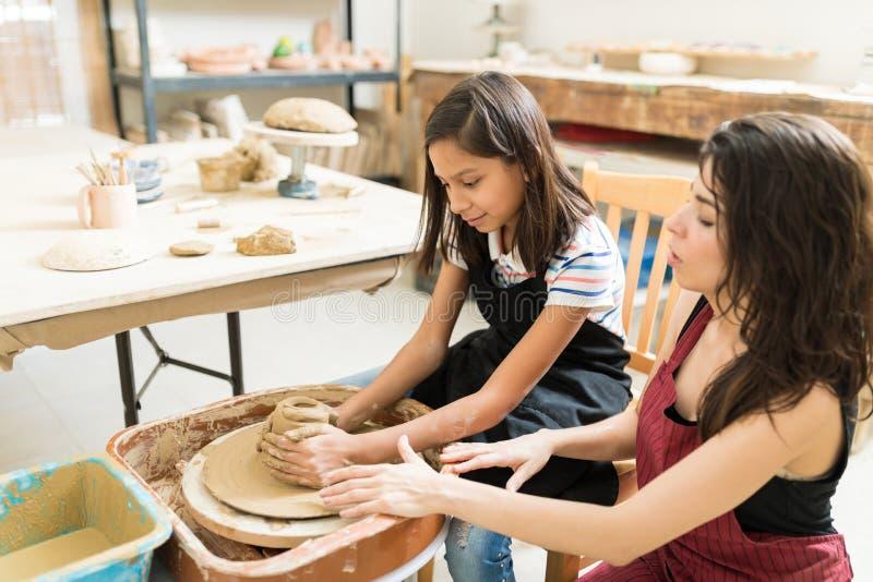 Lehrer Teaching Techniques Of, das dem Mädchen Tonwaren macht stockbild