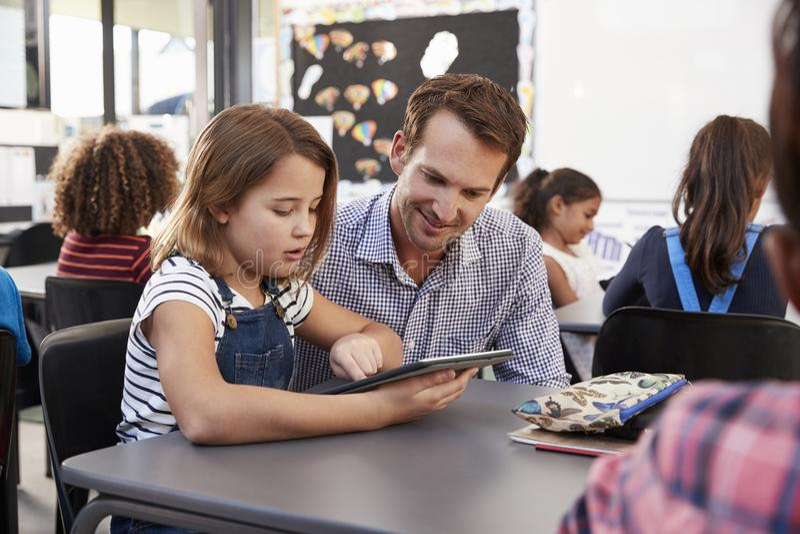 Lehrer und junges Schulmädchen, das Tablette im Klassenzimmer verwendet lizenzfreie stockfotografie