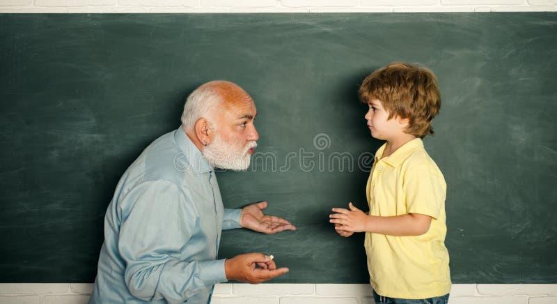 Lehrer und Kind Porträt des überzeugten alten männlichen Lehrers kursteilnehmer Glücklicher Schüler mit Übertafelhintergrund lizenzfreies stockfoto