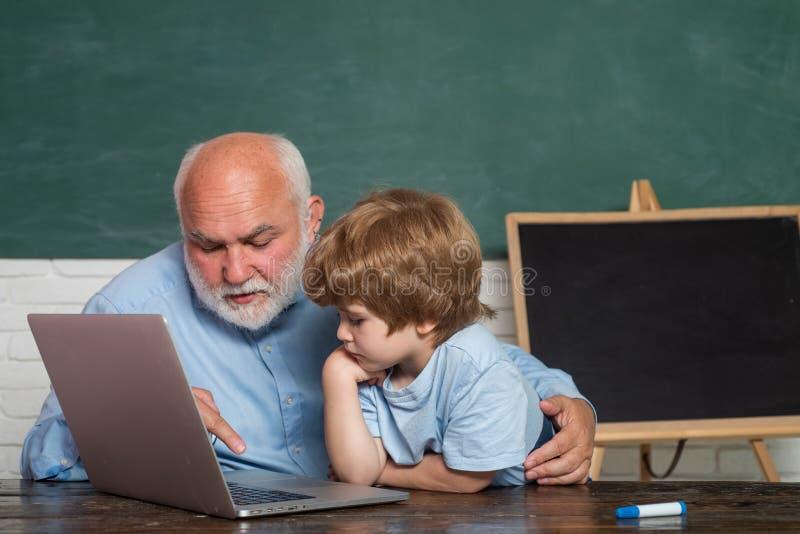 Lehrer und Kind Seins genießt, mit Großvater zu sprechen Vati und Sohn zusammen Junger ernster männlicher Schüler, der herein stu lizenzfreie stockfotos