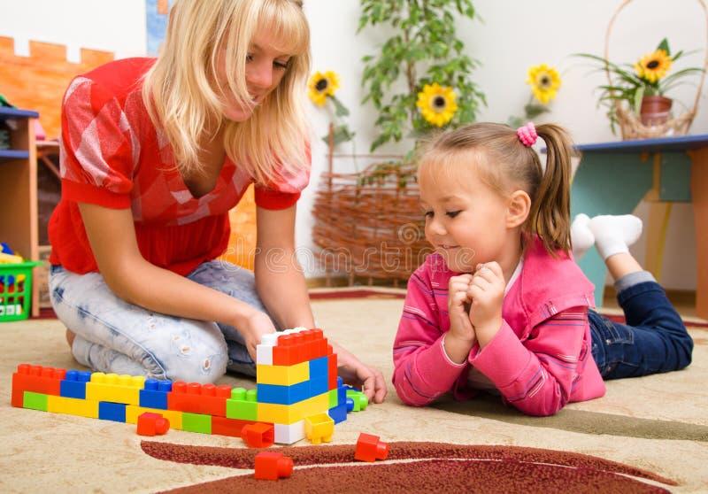 Lehrer und Kind spielen mit Ziegelsteinen stockfoto