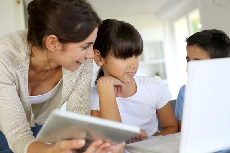 Lehrer und Kinder, die Laptop und Tablette verwenden lizenzfreie stockbilder