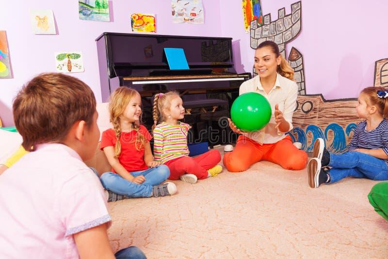 Lehrer und Kinder sitzen im Kreisspiel mit Ball lizenzfreie stockfotos