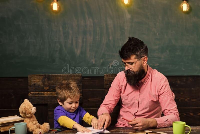 Lehrer und Kleinkind, die am Schreibtisch mit Büchern und Teddybären sitzen Schüler, der mit Schreibheft spielt Strenger Lehrer h stockbild