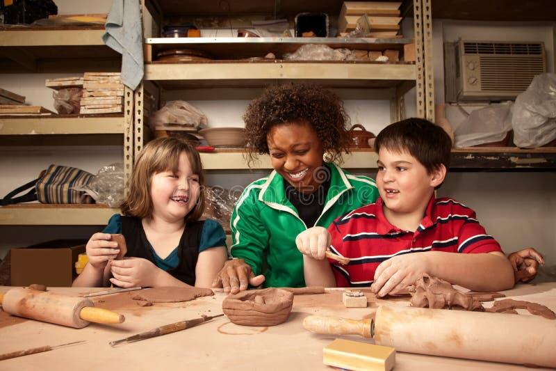 Lehrer und Kursteilnehmer im Lehmstudio stockfoto