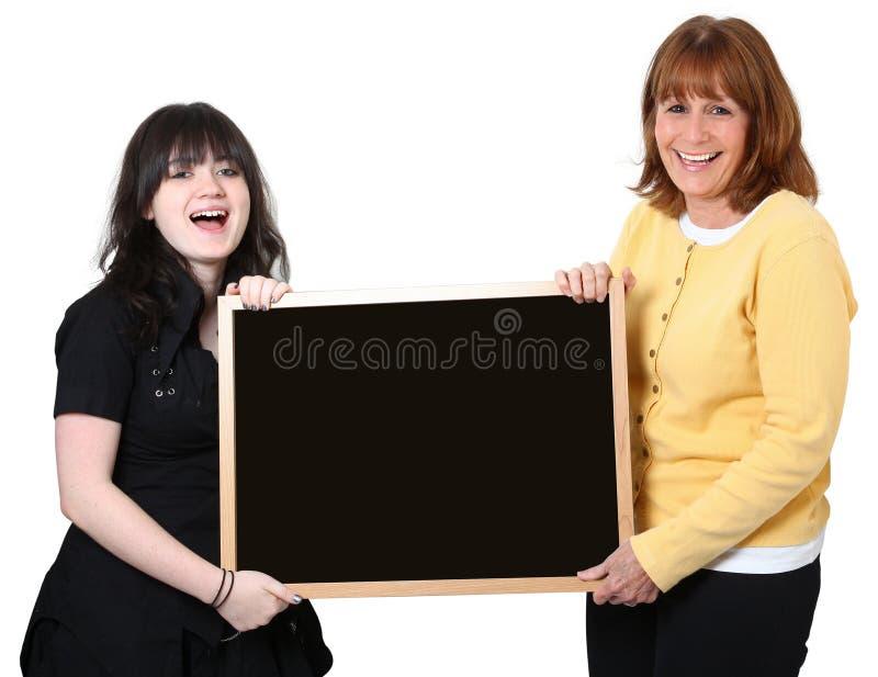 Lehrer und Kursteilnehmer mit Tafel über Weiß stockbild