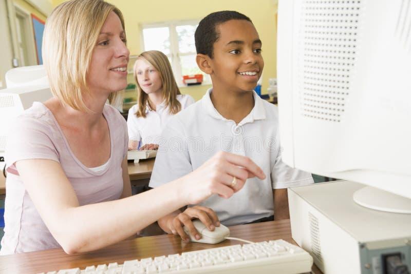 Lehrer und Schüler, die auf einem Computer studieren stockbilder