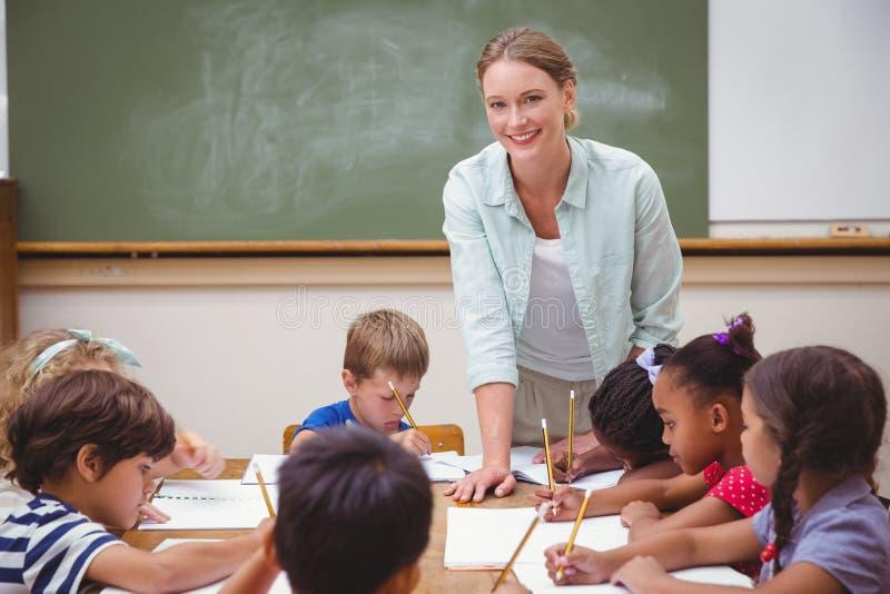 Lehrer und Schüler, die am Schreibtisch zusammenarbeiten stockbild