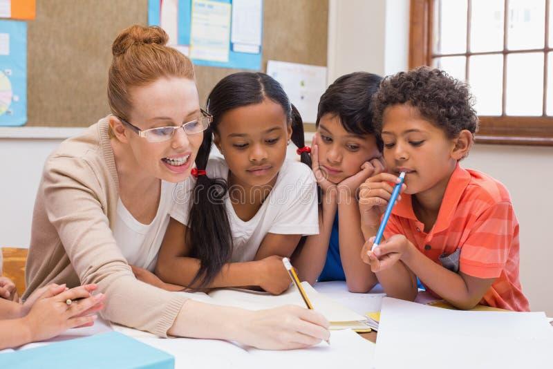 Lehrer und Schüler, die am Schreibtisch zusammenarbeiten lizenzfreie stockbilder