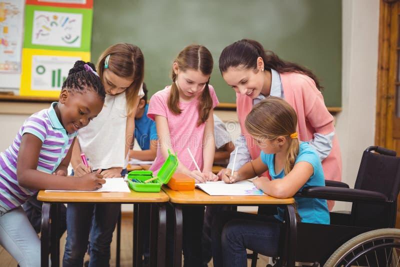 Lehrer und Schüler, die am Schreibtisch zusammenarbeiten lizenzfreies stockfoto
