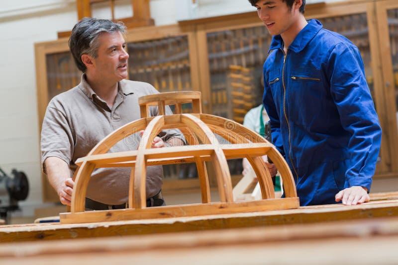 Lehrer und Student, die über einen Holzrahmen sprechen stockfotografie
