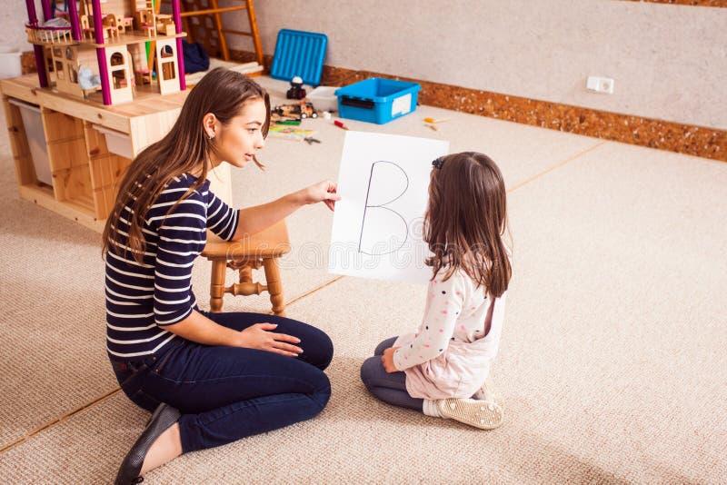 Lehrer unterrichtet das Mädchen lizenzfreie stockbilder