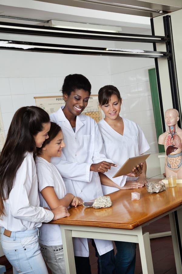 Lehrer Using Digital Tablet mit Studenten am Schreibtisch stockbilder