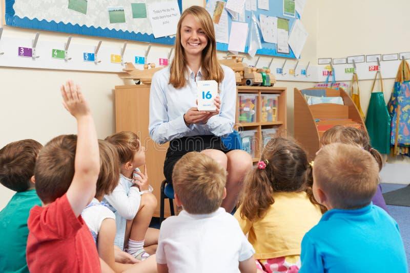 Lehrer Using Flash Cards zum Unterrichten der grundlegenden Klasse von Mathe lizenzfreie stockfotos