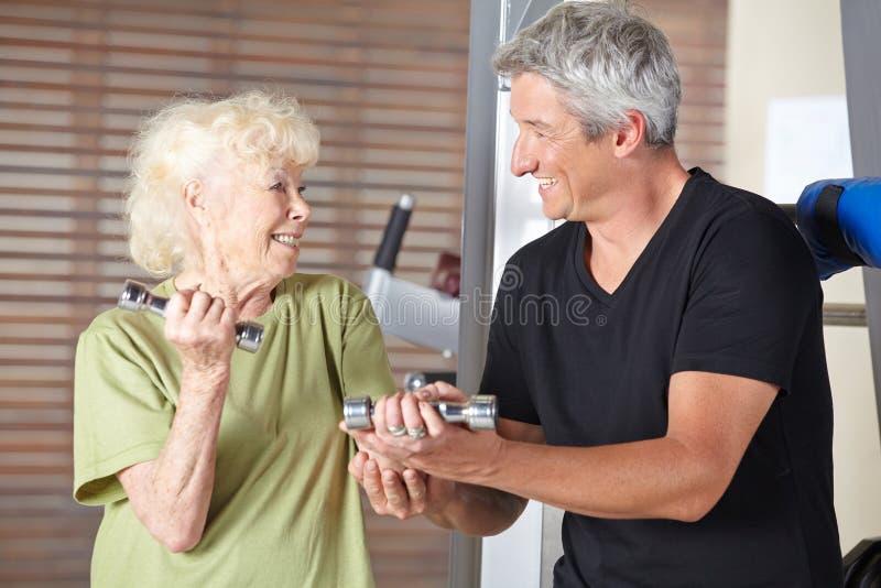Lehrer, welche älterer Frau in der Rehabilitationsturnhalle hilft lizenzfreie stockbilder