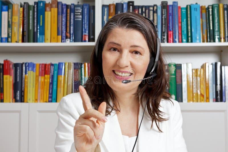 Lehrerfrauenkopfhörer-Mikrofone-learning lizenzfreies stockbild