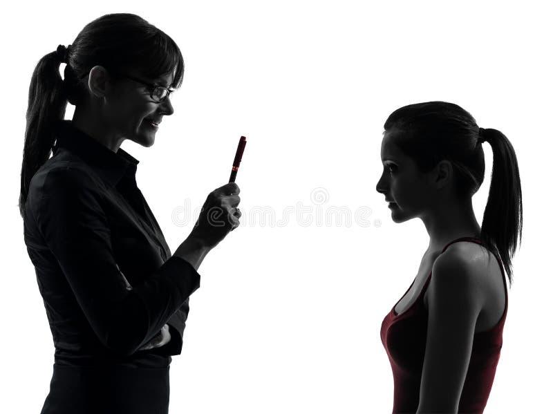 Lehrerfrauenmutterjugendlich-Mädchendiskussion im Schattenbild stockbild