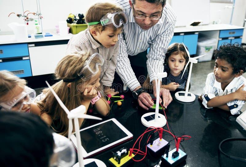 Lehrerhände, die Solarwindmühlenenergieerzeugnis einschalten stockfotografie