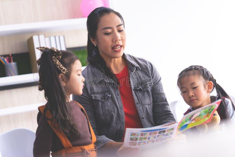 Lehrerlesegeschichtenbuch zu den Kindergartenstudenten stockfoto