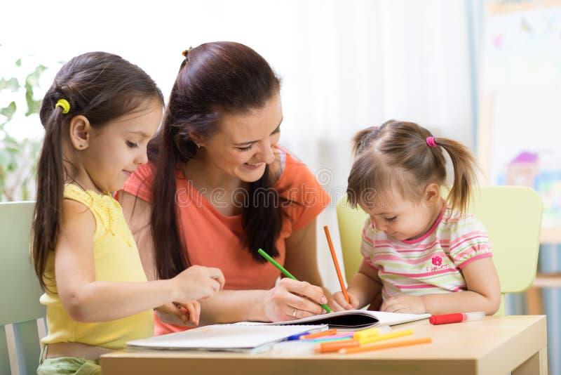 Lehrermutter, die mit kreativen Kindern arbeitet stockfotos